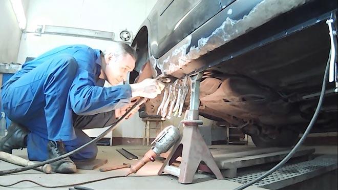 Сварщик ремонтирует машину